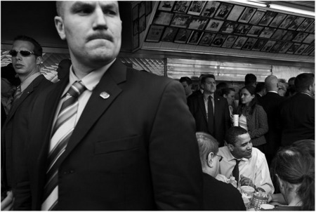 A Secret Service agent keeps watch as Obama lunches on a cheesesteak in Philly.